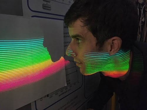 Tilo Steinmetz, Menlo's AstroComb product manager, inspects the comb modes of the ESPRESSO-AstroComb that are projected onto a screen by means of an echelle spectrograph.
