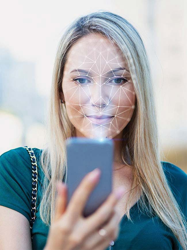 A representation of an NIR system being used for facial recognition. The smartphone emits a diffractive optical element (DOE) dot-grid pattern (invisible to the user) that is cast on the face. An IR camera inside the phone captures the reflection of NIR light and analyzes deformations of the grid pattern to determine 3D contours of the face for identification.