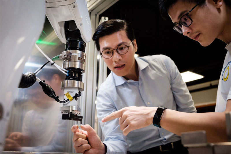 Associate professor Quang-Cuong Pham (l) working with lead engineer Tien-Hung Pham on the robot Archimedes. Courtesy of NTU Singapore.