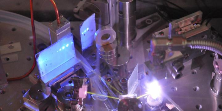 Ultrafast pulses of extreme ultraviolet light are created in a gas jet of white plasma, and are visible as blue dots on a phosphor screen as well as yellow beams from oxygen fluorescence. Courtesy of Research to Reality/UBC.