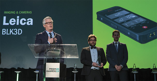 Hugh Baertlein, a vice president of Hexagon Geosystems, accepts the 2019 Prism Award in the Imaging and Cameras category on behalf of Leica Geosystems. Courtesy of SPIE/Joey Cobbs Photography.