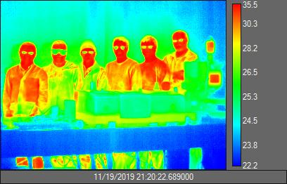 Taken with a long-wave infrared camera, this image of researchers in Mikhail Kats' lab shows distinct color variations across areas that are warmer (faces and bodies) and cooler (the table). Courtesy of the Kats group. UW-Madison.