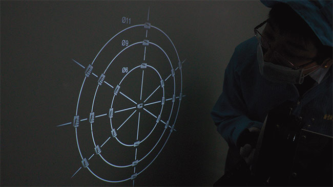 An operator performs a test using reverse projection. The circles labeled 11, 9, and 6 correspond to the image circles of 2/3-in., 1/1.8-in., and 1/3-in. sensors, respectively.  Courtesy of Edmund Optics Inc.