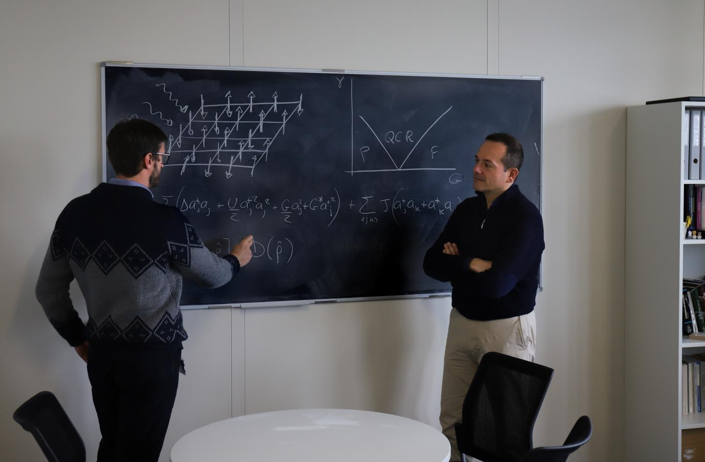 Riccardo Rota and Vincenzo Savona, the two EPFL physicists leading the study, working on the design of their quantum simulator. Courtesy of R. Ravasio/EPFL.
