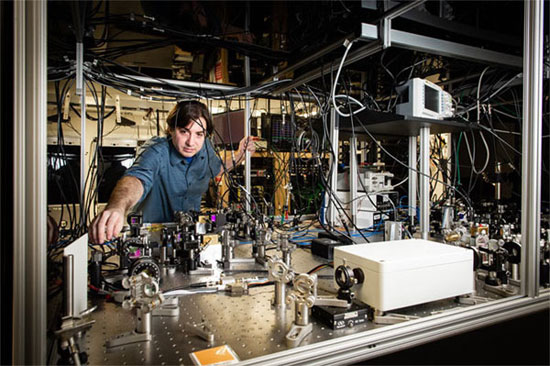 """Quantum Back Action Measurement Could Improve Sensitivity of Gravitational-Wave Detectors  BATON ROUGE, La., March x, 2019 &mdash; Researchers at Louisiana State University (LSU) have defined a broadband, off-resonance measurement of quantum radiation pressure noise (QRPN) in the audio band, at frequencies relevant to gravitational wave detectors. The noise spectrum obtained by the team shows effects due to QRPN between about 2 kilohertz and 100 kilohertz. The results of the research could lead to methods to improve the sensitivity of gravitational-wave detectors by developing techniques to mitigate the imprecision in back action measurements, thus increasing the chances of detecting gravitational waves. The researchers developed devices, housed in miniature models of detectors like LIGO, that made it possible to observe quantum effects at room temperature. The devices consist of low-loss, single-crystal microresonators. Each mirror pad is the size of a pin prick and is suspended from a cantilever. When a laser beam is directed at one of the mirrors, the beam that is reflected causes enough fluctuating radiation pressure to bend the cantilever structure, causing the mirror pad to vibrate and create noise. Gravitational wave interferometers use high-power lasers in order to minimize the uncertainty caused by the measurement of discrete photons and maximize the signal-to-noise ratio. These high-power beams increase position accuracy but do so at the expense of back action in the form of QRPN. Advanced LIGO and other second and third generation interferometers will be limited by QRPN at low frequencies when running at their full laser power; but the LSU team, which includes collaborators at MIT, offers clues as to how scientists can work around this when measuring gravitational waves. """"Given the imperative for more sensitive gravitational wave detectors, it is important to study the effects of quantum radiation pressure noise in a system similar to Advanced LIGO, which"""