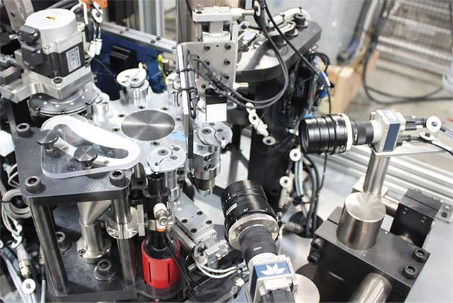 An inspection of valve assemblies designed to regulate the flow of gasoline into the carburetor. The main dial rotates so each completed assembly is moved within view of two Teledyne DALSA Genie Nano cameras and analyzed for height, alignment, concentricity, and runout. Courtesy of Matrix Design.