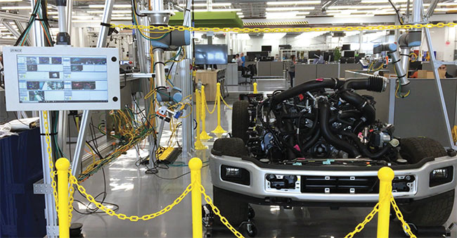 A robot equipped with two cameras performs a flexible inspection on an engine and chassis. Courtesy of Ford Motor Co..