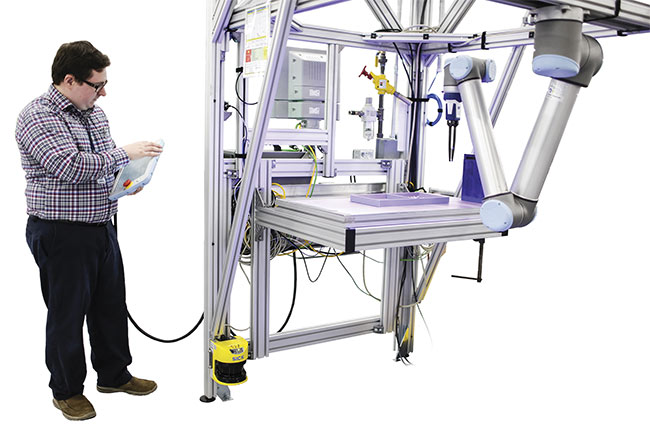 Walter LaPlante, a systems engineer at Ford Motor Co., works with a collaborative robot that operates safely alongside people without needing a protective cage. Such robots avoid people and objects through the benefit of 3D vision. Courtesy of Ford Motor Co..