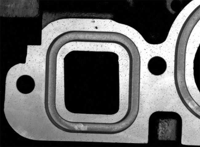 An engine block (top must be inspected for pores (bottom) and other defects. Flexible camera positioning solves this challenging vision task. Courtesy of LEONI Engineering Products and Services.