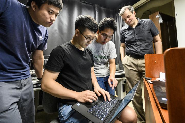 UW graduate students (left to right) Xiaochun Liu, Ji-Hyun Nam, and Toan Le work with assistant professor and principal investigator Andreas Velten (right) in the Computational Optics lab inside the Medical Sciences Building at the University of Wisconsin-Madison.