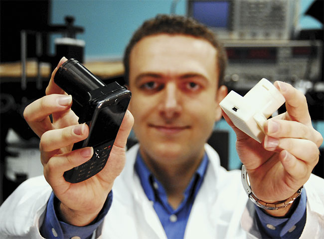 Aydogan Ozcan displays hand-held, lens-free microscopes. The black one (left) is installed on a phone and uses the phone's CMOS imager for lens-free microscopy of a specimen. The white prototype (right) is a stand-alone hand-held lens-free microscope that is controlled by a laptop using a USB cable. This stand-alone version weighs less than 50 g. Courtesy of Ozcan Lab/UCLA.