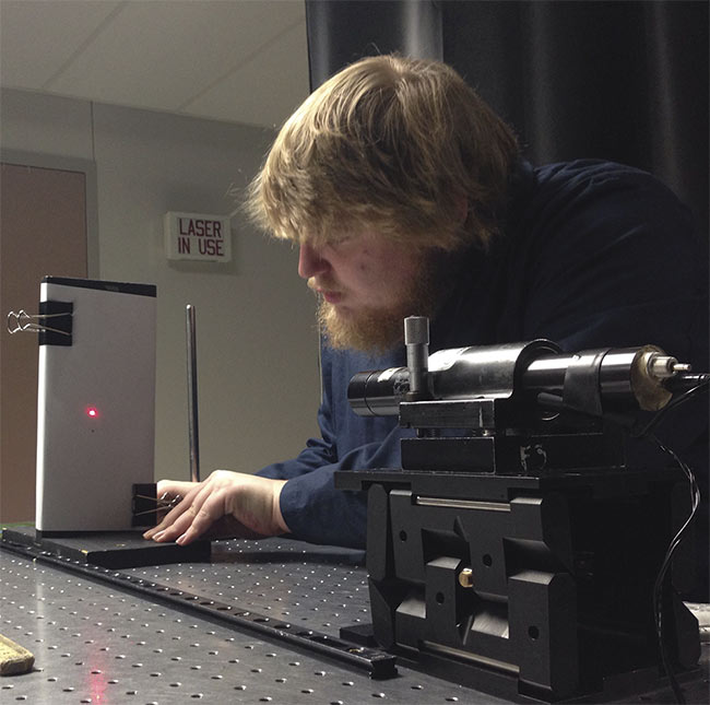 Student Joey Lee sets up a Class 1 laser experiment at IHCC. Courtesy of LASER-TEC.