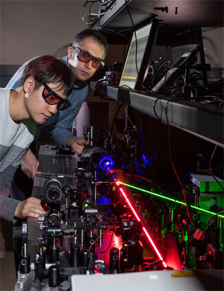 Georgia Tech researchers Kyu-Tae Lee and Mohammad Taghinejad demonstrate frequency doubling on a slab of titanium dioxide using a red laser to create nonlinear effects with tiny triangles of gold. The blue beam shows the frequency-doubled light and the green beam controls the hot-electron migration. Courtesy of Rob Felt, Georgia Tech.