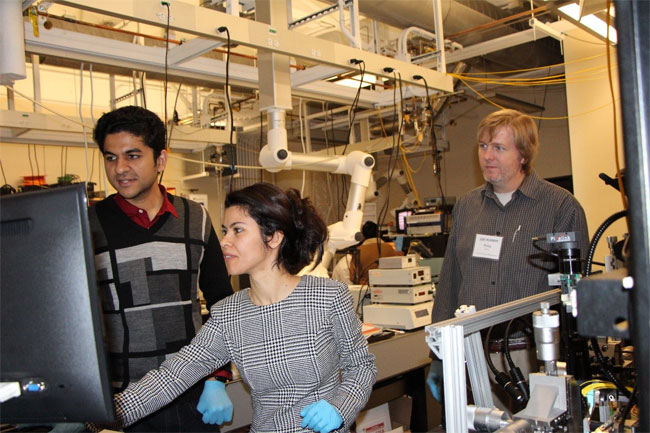 Bootcamp student and Bridgewater State University professor, Elif Demirbas, learning how to perform grating coupling from a fiber to a chip with instruction from Robin Singh, while Phillip Wilcox, an engineer from U.S. Army CCDC, looks on. Courtesy of MIT.