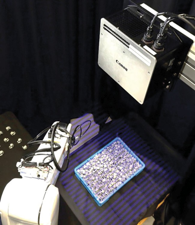 Overhead view of a machine vision-guided robot selecting parts from a bin. Courtesy of Canon.