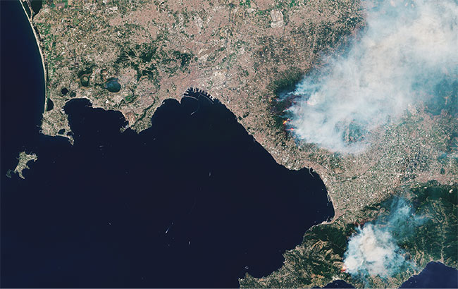 Various bands from the MSI of Sentinel-2 are used to reveal different processes on the ground. In July 2017, wildfires broke out in Italy, including blazes on the slopes of Mount Vesuvius, near Naples, that led some to believe the volcano was erupting again. A natural color band combination that uses the visible bands, plus highlights from the shortwave infrared part of the spectrum, shows the extent of the disaster and smoke (top). Shortwave infrared bands penetrate the smoke of the fire (bottom). Courtesy of USGS/ESA.