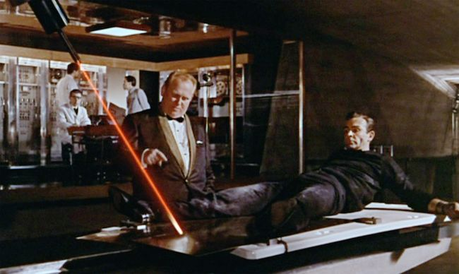 Auric Goldfinger (Gert Frobe, left) looks on as James Bond (Sean Connery, right) stares down an industrial cutting laser. Courtesy of MGM/UA.