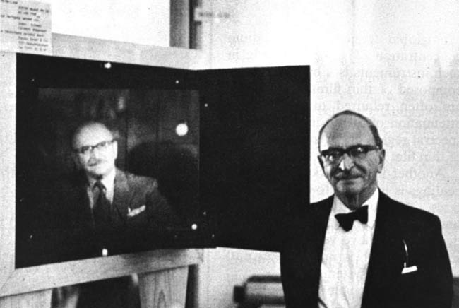 Dr. Dennis Gabor, winner of the 1971 Nobel Prize for physics, stands beside a portrait hologram made by McDonnell Douglas Electronics. Courtesy of McDonnell Douglas Electronics.