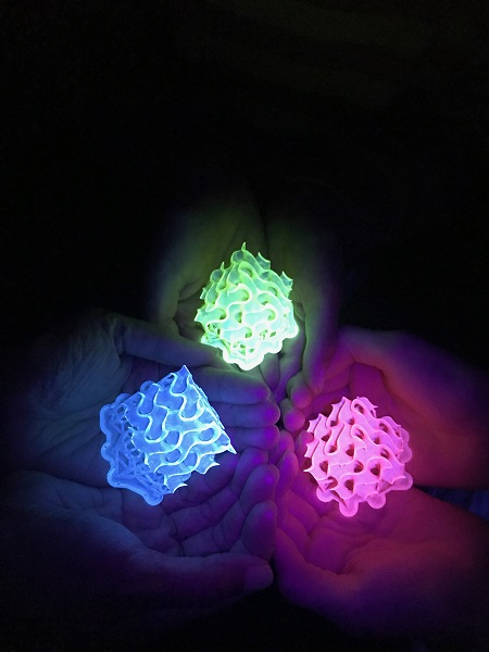 This image shows glowing 3D-printed gyroids made with bright SMILES materials. Courtesy of Amar Flood.