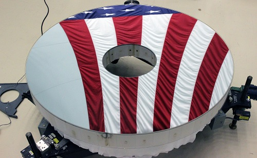 The Roman Space Telescope's primary mirror reflects an American flag. Its surface is figured to a level hundreds of times finer than a typical household mirror. Courtesy of L3Harris Technologies.