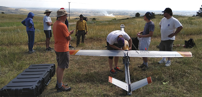 Black Swift Technologies' SuperSwift unmanned aircraft system is prepared for flight with its sensor payload. A prescribed burn appears in the distance. Courtesy of Black Swift Technologies.
