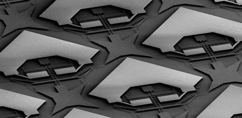 "Partial SEM image of the switch matrix: The whole structure patterned in the top silicon layer by dry etching seems to ""float"" as the oxide is removed. Each matrix unit contains an electrostatic comb drive that can selectively move portions of the waveguides to establish a desired light path from one of the 32 input ports to one of the 32 output ports. Courtesy of SPIE via Han et al."