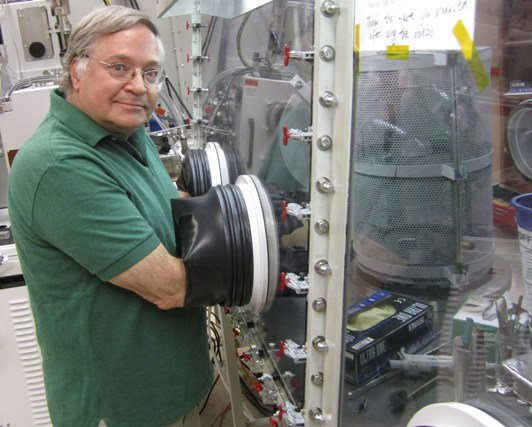 University of Utah physicist Z. Valy Vardeny works in a glove box where light-emitting polymers are studied under clean conditions.